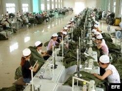 Una mujeres trabajan en una fábrica de ropa en China.