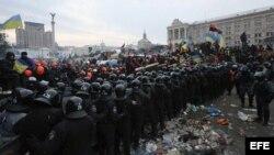 Agentes antidisturbios se enfrentan a los manifestantes durante otro día de protestas en la Plaza de la Independencia de Kiev (Ucrania), hoy, miércoles 11 de diciembre de 2013.