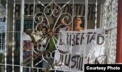 Jorge Cervantes muestra un cartel antigubernamental en su casa de Contramaestre.