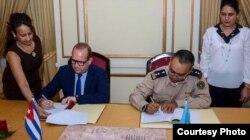 William Pérez González, vicejefe de la Aduana de Cuba, y Bob Van Den Bergher, representante de la ONUDD, firman un memorando para la inspección de contenedores.
