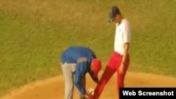 El entrenador hace un ritual al lanzador durante los momentos pevios a la final.