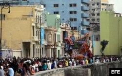 """Personas caminan por el Malecón en la exposición """"Detrás del Muro"""" como parte de la XII Bienal de Arte de La Habana."""