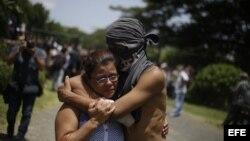 Un estudiante abraza a un familiar luego de salir del resguardo en la parroquia Divina Misericordia, en Managua.