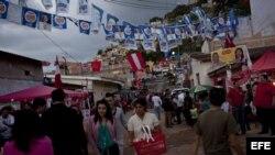Varias personas caminan en Tegucigalpa (Honduras). Las votaciones generales en el país finalizaron con una masiva afluencia de votantes y sin mayores incidentes.