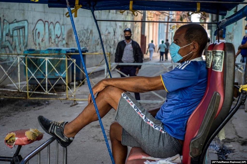 Ein Fahrradtaxifahrer wartet auf Kunden vor einem Tor, wo die Polizei zur Eindämmung des Coronavirus den Zugang zu einem Viertel kontrolliert (22. Februar 2021). | Bildquelle: Radio Televisión Martí | Bilder sind in der Regel urheberrechtlich geschützt
