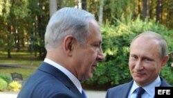 El presidente ruso, Vladimir Putin (c), conversa con el primer ministro israelí Benjamin Netanyahu (izda), durante la reunión que han mantenido en su residencia de Novo-Ogaryovo, afueras de Moscú, Rusia, el 21 de septiembre del 2015.