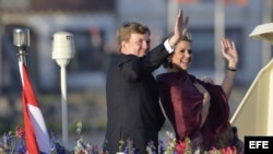 El rey Guillermo-Alejandro de Holanda (i) y la reina Máxima (d), saludan a los espectadores durante su paseo en barco por el río Ij hoy, martes 30 de abril de 2013, tras la ceremonia en la que Guillermo-Alejandro fue proclamado rey