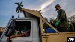 Militares movilizados por el gobierno cubano llegan el miércoles a una plaza de La Habana para desinfectar el área (Foto: Yamil Lage/AFP).