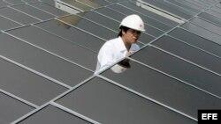 Un empleado de Hong Kong Electric (HKE) comprueba el funcionamiento de los paneles solares recién instalados en el tejado de la estación eleéctrica Lamma de HKE, en Hong Kong (China).