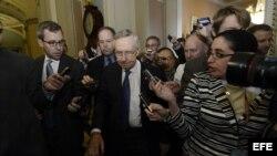 El líder de la mayoría demócrata del Senado estadounidense, Harry Reid (c), avanza rodeado por numerosos periodistas tras su reunión con el líder de la minoría, Mitch McConnell (no aparece), en el Capitolio, Washington (Estados Unidos), hoy, lunes 14 de o