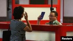 Un oficial de inmigración chequea el pasaporte de una mujer en el Aeropuerto Internacional José Martí de La Habana.