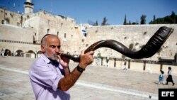"""Un judio ultraortodoxo hace sonar un """"Shofar"""" con el que se pide a Dios que se perdonen todos los pecados, delante del muro de las lamentaciones antes del comienzo de la festividad del Yom Kippur, ó """"Día del Perdón""""."""