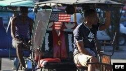 Un bicitaxista con la bandera de EEUU decorando su vehículo (18/12/2014).