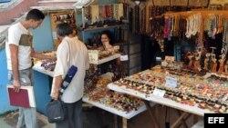 Dos hombres compran artesanías cubanas en La Habana (Cuba).