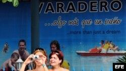 Dos mujeres cubanas hospedadas en hoteles de Varadero, toman fotos con sus cámaras digitales.