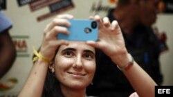 """La cubana Yoani Sánchez, autora del blog """"Generación Y"""", toma una foto durante su primera jornada de visita a Brasil hoy, lunes 18 de febrero de 2013, en Feira de Santana."""