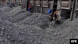 Trabajadores amontonan carbón en una estación de procesamiento de Beishan, cercano a Shanyang, China, que es mayor consumidor de carbón.