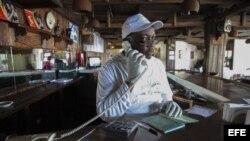 Un recepcionista liberiano habla por teléfono usando guantes en sus manos para evitar el contacto con el mortal virus del ébola en la capital Monrovia.