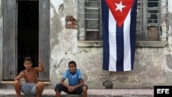 Dos niños posan para una fotografía al frente de una casa con la bandera cubana.