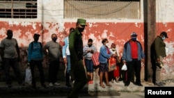 Un agente del MININT controla una cola en un mercado de La Habana. REUTERS/Stringer