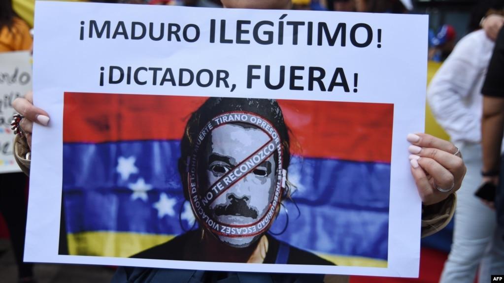 Manifestante muestra pancarta calificando de dictador a Maduro