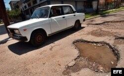 Un automóvil trata de evitar los baches de las calles de La Habana, Cuba.
