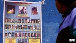"""Una persona observa uno de los carteles en el municipio de Monterrey,925 kilómetros de la capital mexicana que ofrecen recompensas de hasta 5 millones de dólares por información que lleve a la captura de el narcotraficante Joaquín Guzmán Loera, alias """"El"""