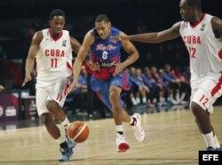 Richard Chanel (c) de Puerto Rico disputa el balón contra dos jugadores cubanos.