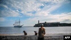 Un cubano en el Malecón observa la llegada de un buque español a la Bahía de La Habana.
