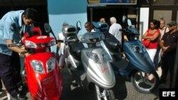 Cubanos observan distintos modelos de motos eléctricas en un centro comercial en La Habana. (Archivo)