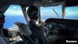 Un miembro de la Guardia Costera de los Estados Unidos pilota un avión HC-144 Ocean Sentry durante una misión de patrullaje en el Estrecho de Florida, el 17 de julio de 2021. REUTERS / Marco Bello