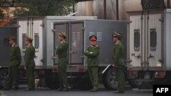 Policías custodian transporte para prisioneros en la Corte de Hanoi.
