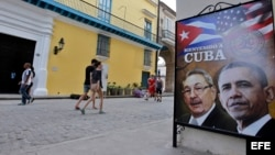 Transeúntes caminan cerca a una imagen de Barack Obama y Raúl Castro. #ObamaEnCuba.
