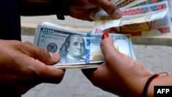 Una mujer cambia dólares en una calle de La Habana en diciembre de 2019. (YAMIL LAGE / AFP)