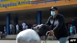 Un cubano residente en Estados Unidos arriba cargado de paquetes al Aeropuerto Internacional José Martí de La Habana. ( Yamil LAGE / AFP)