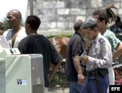 Un policía cubano identifica a dos ciudadanos afroamericanos en la zona de La Habana Vieja.