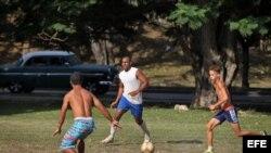 óvenes juegan fútbol en un parque de La Habana