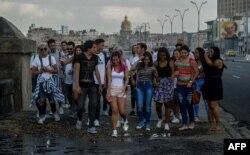 Un grupo de jóvenes camina por el Malecón de La Habana.
