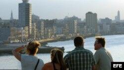 Un grupo de turistas observan La Habana, al atardecer, desde la fortaleza de El Morro, al otro lado de la bahía