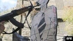 Una persona apunta con un arma a una figura de cartón que representa al presidente sirio, Bachar al-Assad, durante una manifestación contra el régimen sirio. Los rebeldes sirios han tomado el control en las últimas horas de ciudad fronteriza con Jordania