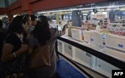 Desde fuera, varias personas contemplan los electrodomésticos a la venta en una de las tiendas que abrieron el lunes en La Habana (Foto: Yamil Lage/AFP).