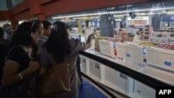 Desde fuera, varias personas contemplan los electrodomésticos a la venta en una de las tiendas que abrieron en octubre en La Habana (Foto de Archivo/Yamil Lage/AFP).
