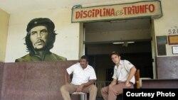 """En Cuba dos jóvenes agentes de seguridad sentados bajo el lema revolucionario """"Disciplina es triunfo"""" (Blog 3rd Culture Cafe)."""