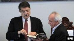 El escritor nicaragüense Sergio Ramírez (i) firma un libro a su colega hondureño Julio Escoto (d).