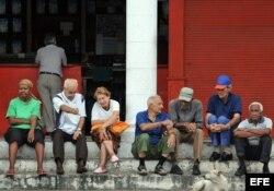 Un grupo de ancianos conversa en la puerta de una bodega.