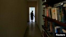Una mujer camina cerca de un librero en su apartamento en La Habana. REUTERS/Claudia Daut