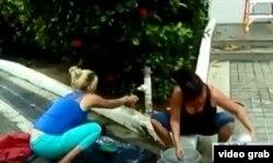 Lisandra Faray, opositora cubana, toma agua de un grifo junto a la calle para lavar la ropa. Faray y otros 15 cubanos están plantados hace seis semanas ante la sede de la ACNUR en Trinidad -Tobago (America Teve)
