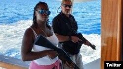 John McAfee junto a una mujer en su yate, sosteniendo armas de asalto. (Twitter/@officialmcafee)