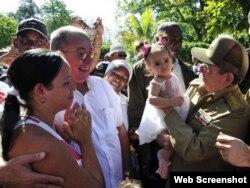 Raúl Castro carga a una niña durante su paseo por las calles de Santiago de Cuba.