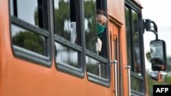 Una mujer que lleva nasobuco se asoma por la ventanilla de un ómnibus en La Habana (Yamil Lage/AFP).
